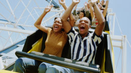 Couple riding on roller coaster with hands up in air, screaming